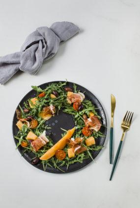 Meloņu salāti ar prošuto, rukolu, Kalamatas olīvām un tomātiem